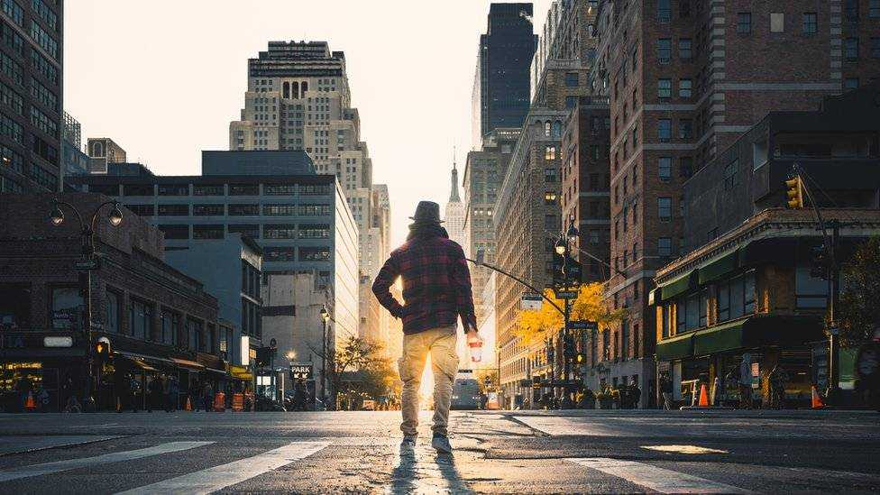 A man with his back turned to stand on an empty New York street.